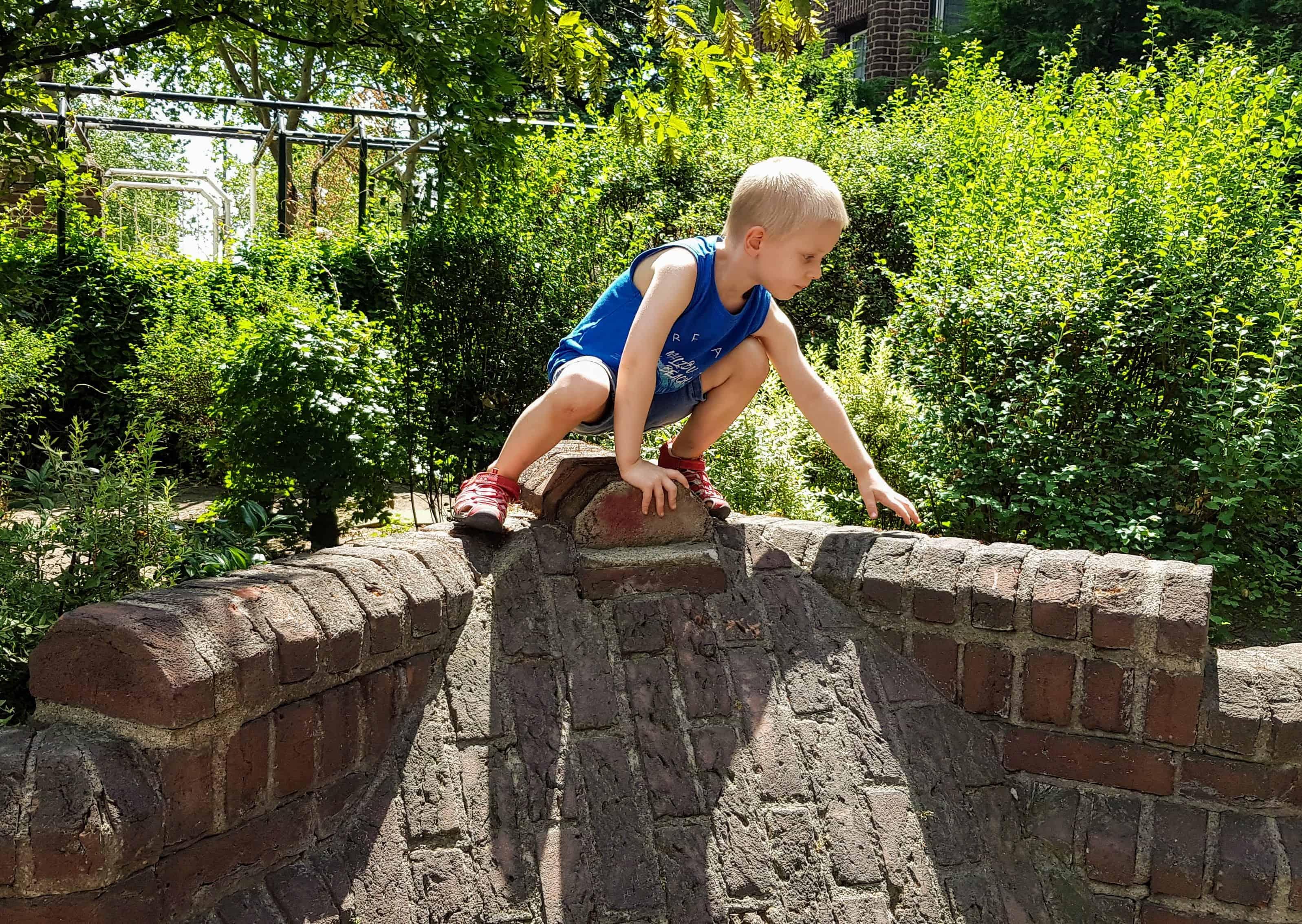 Kind klettert auf der Mauer